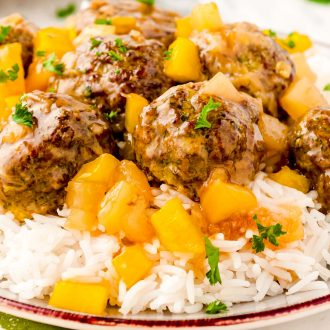 Close up photo of sweet and sour meatballs on a bed of white rice with pineapple.