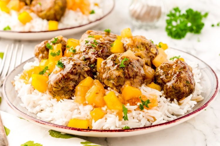 Close up photo of sweet and sour meatballs with pineapple on a plate of white rice.