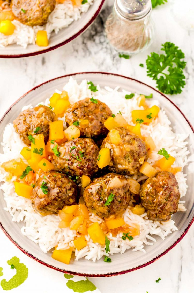 Overhead photo of a plate of white rice topped with sweet and sour meatballs.