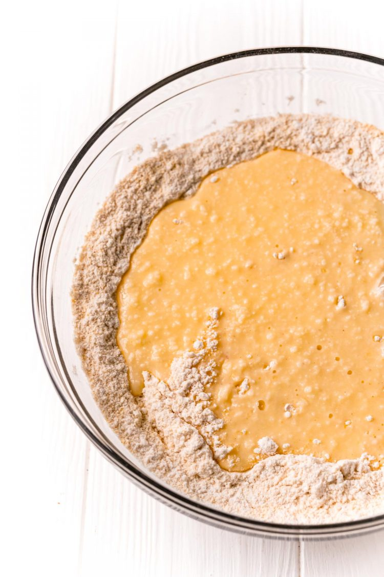 Wet ingredients being poured into a mixing bowl of dry ingredients to make cornbread.