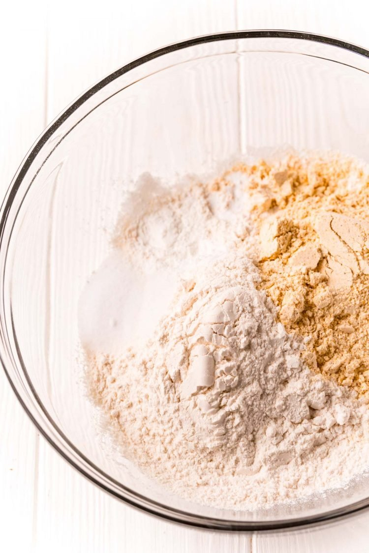 Flour, cornmeal, and sugar in a glass mixing bowl.