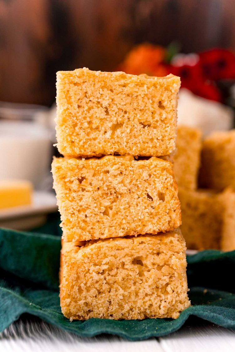 Three slices of cornbread stacked on top of each other on a green napkin.