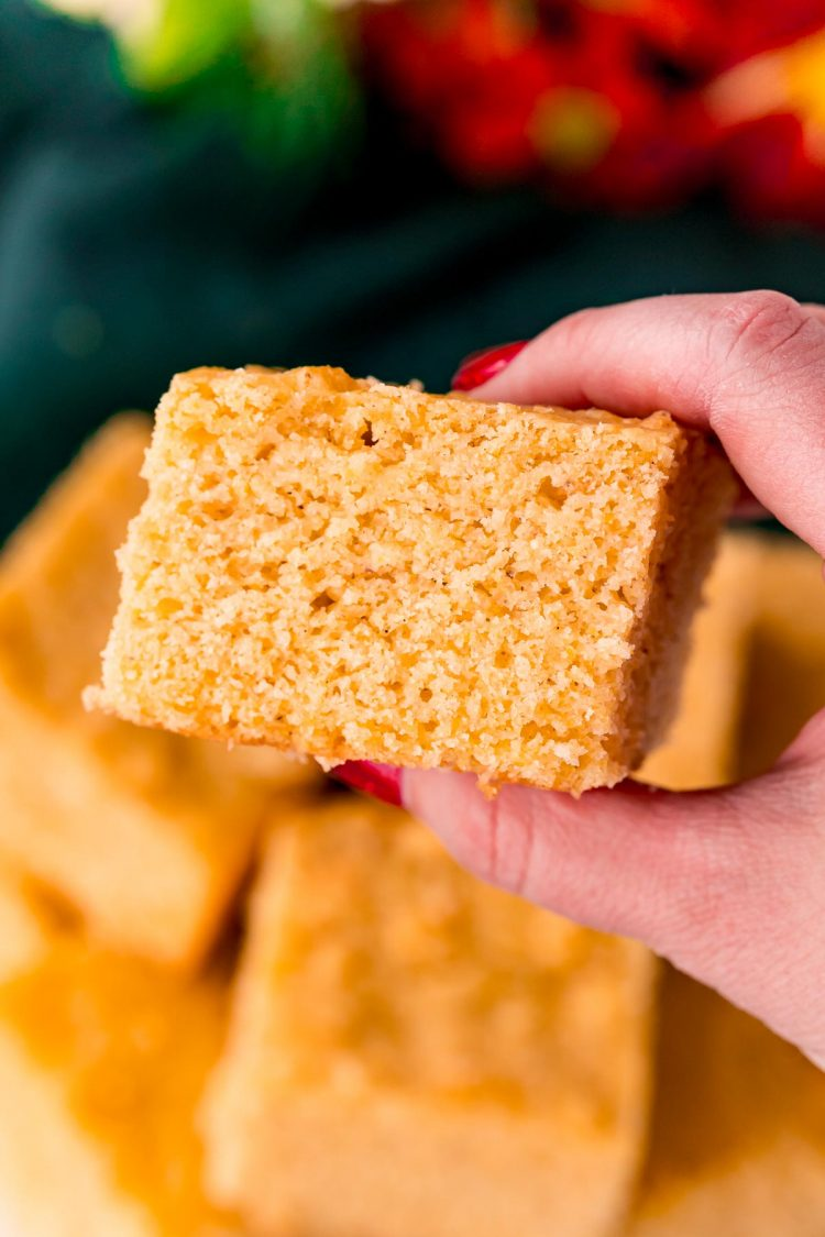 A woman's hand holding a slice of cornbread.