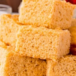 Close up photo of corn bread slices stacked on top of each other on a white plate.