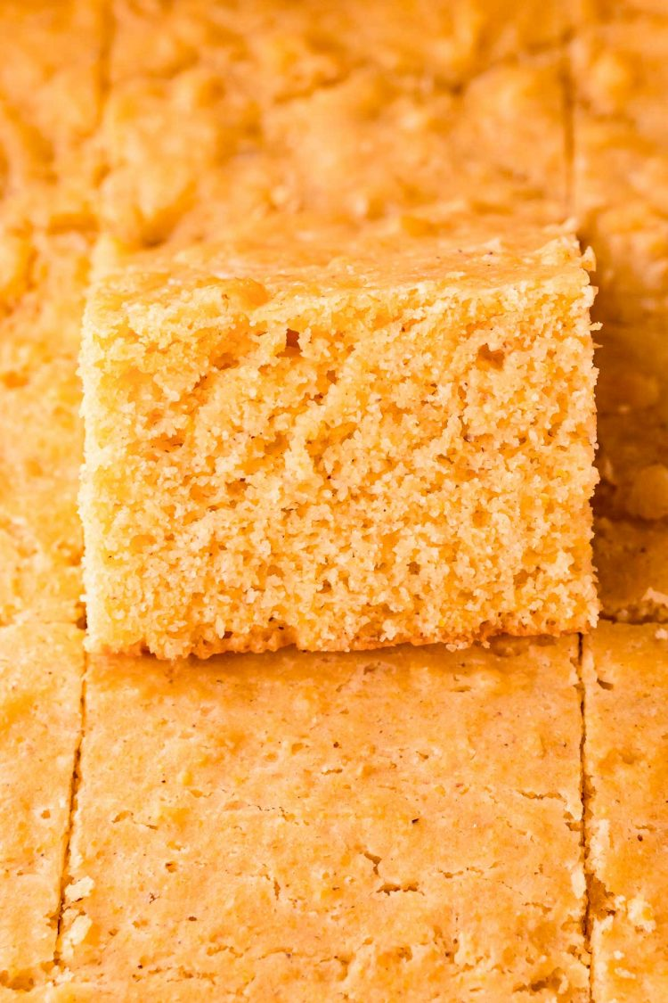 Close up photo of a pan of cornbread where one slice is tipped up out of the pan.