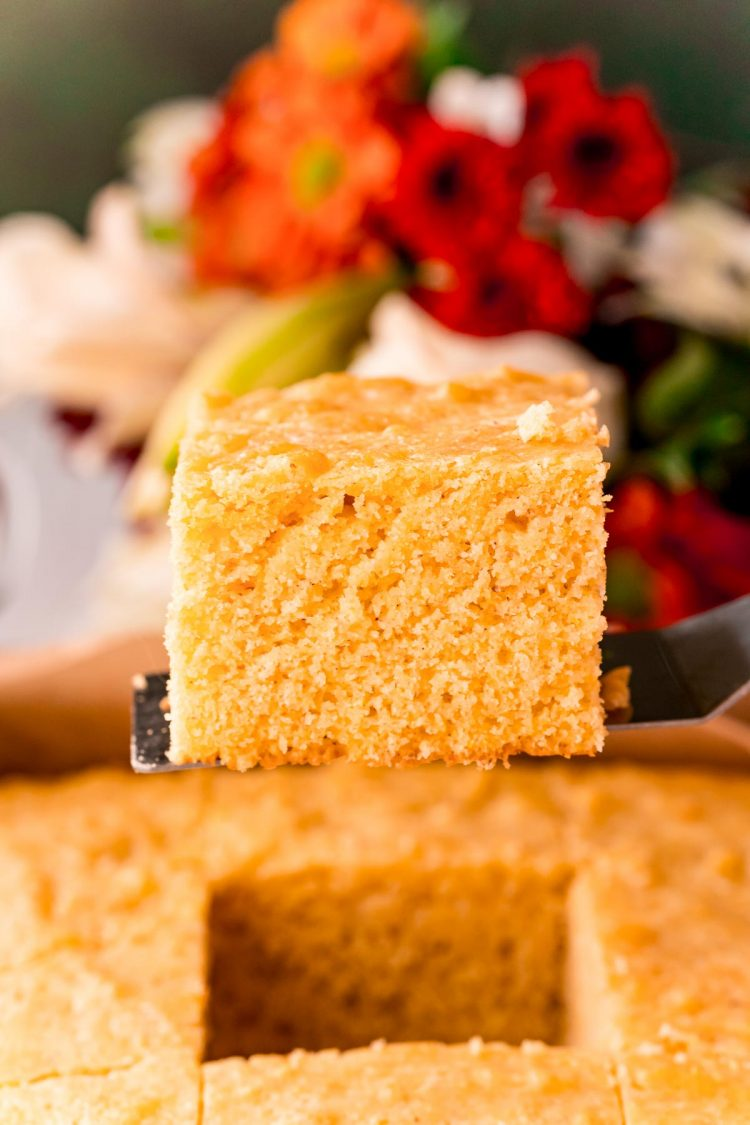 A slice of cornbread being lifted out of a baking pan.