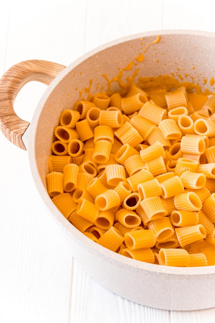 Pasta being added to a pot filled with butternut cream sauce.