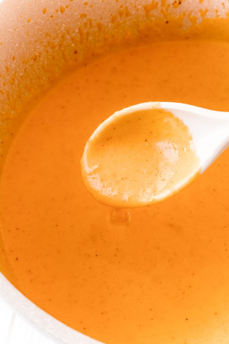 Butternut cream sauce in a pan being scooped up with a white spoon.