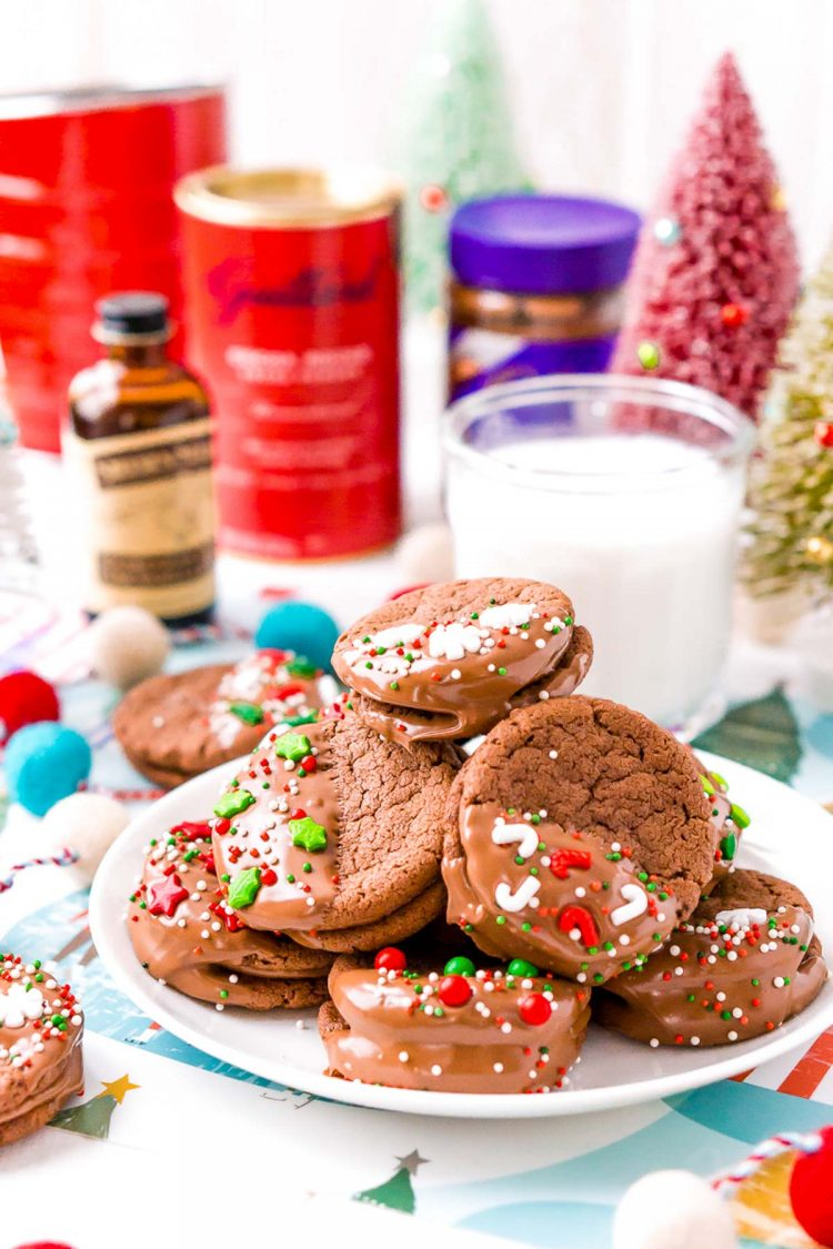 A plate of chocolate cookies decorated for the holidays with ingredients in the background.