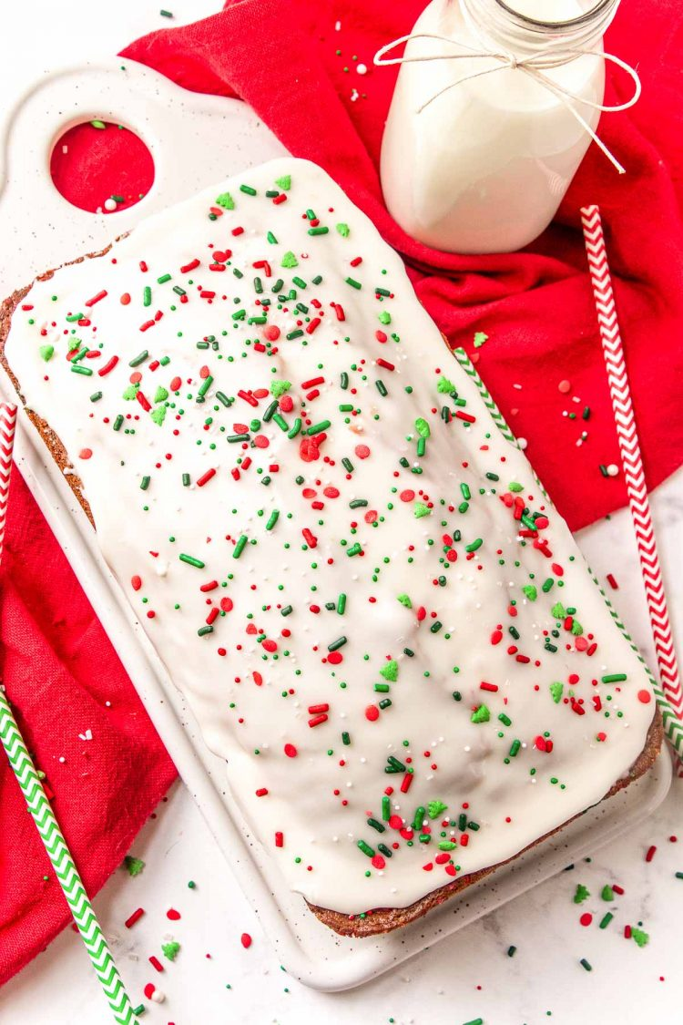 A loaf of quick bread with christmas sprinkles on a white serving tray.