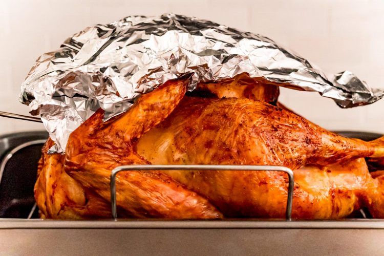 Aluminum foil covering the top portion of a roasted turkey.