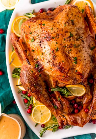 Overhead photo of a roasted turkey on a white platter with lemons, herbs, and cranberries around it.