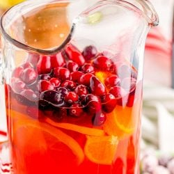 Close up photo of mimosa punch in a pitcher with cranberries.