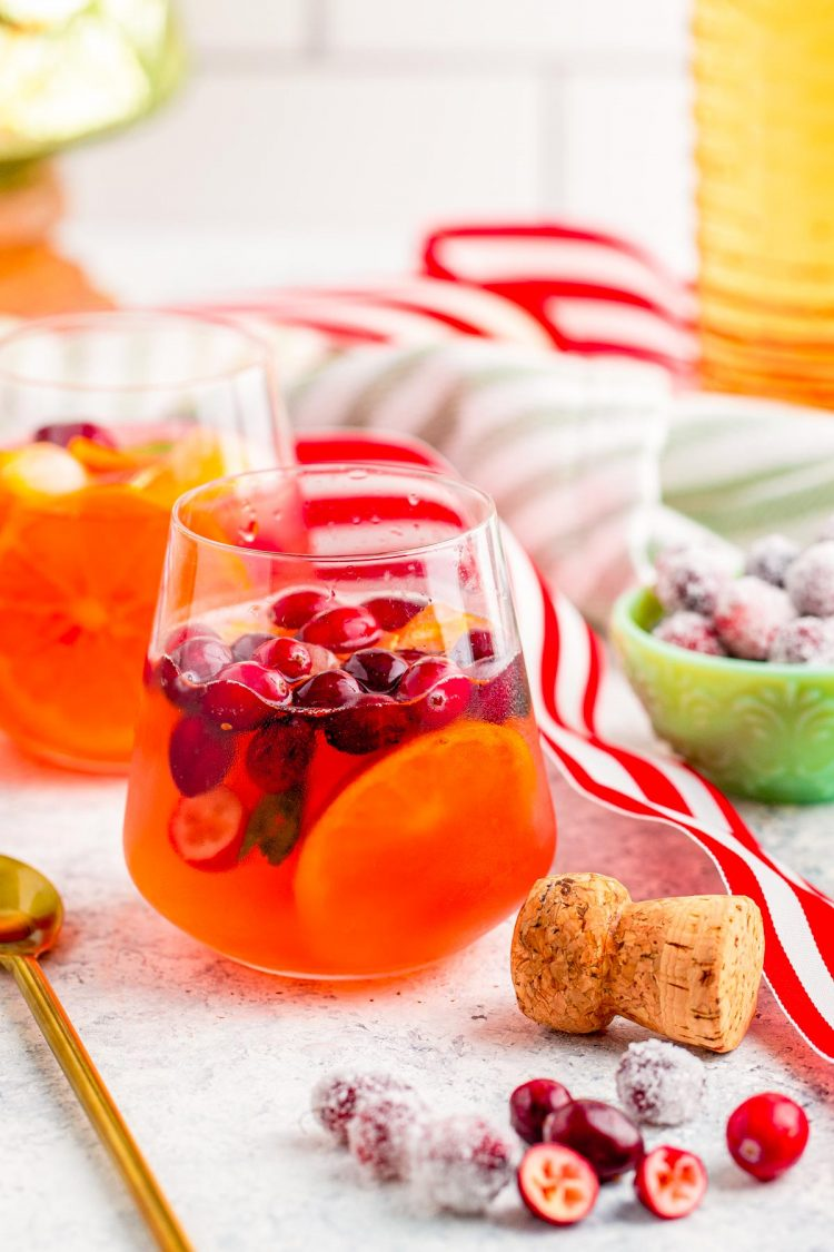 Glass of christmas mimosa punch on a table with holiday decor scattered around.