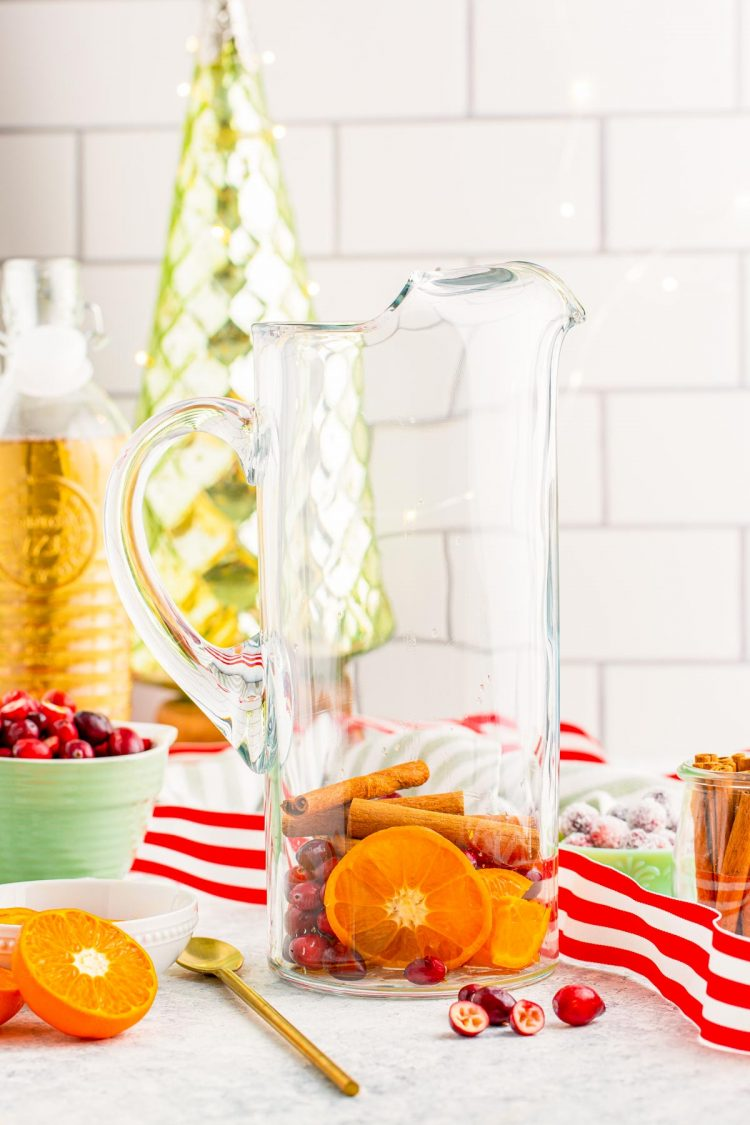 Fruit and cinnamon sticks in a pitcher to make punch.