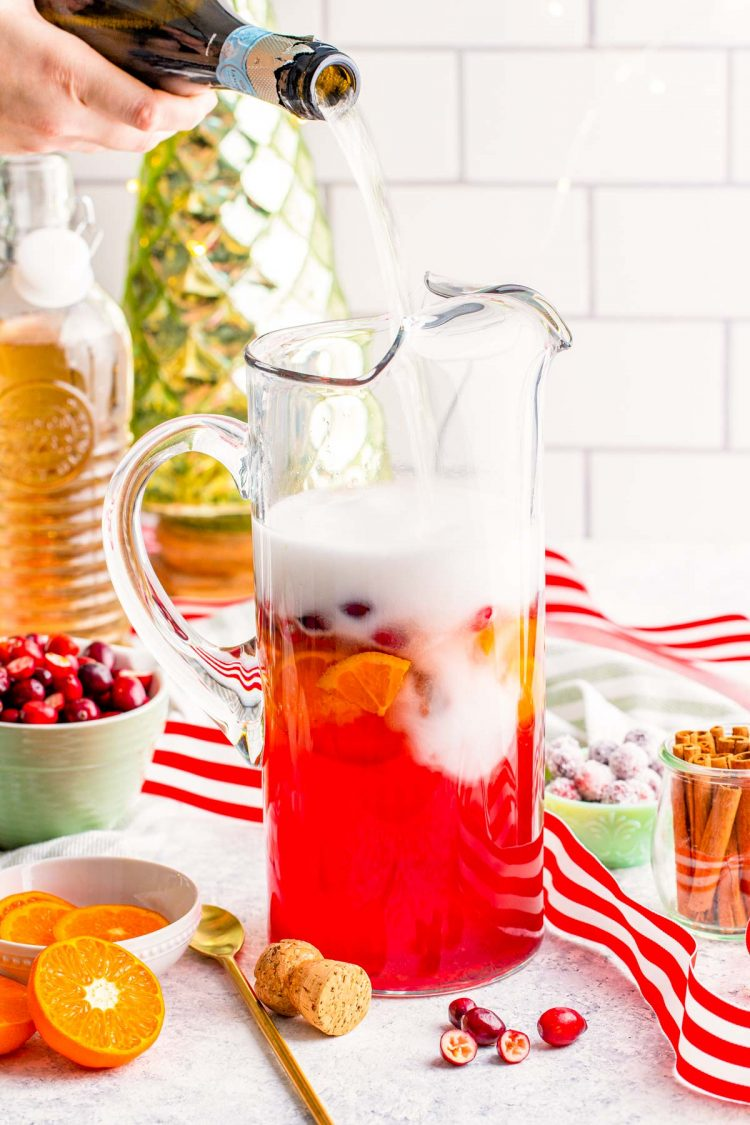 Prosecco being added to a pitcher to make punch.