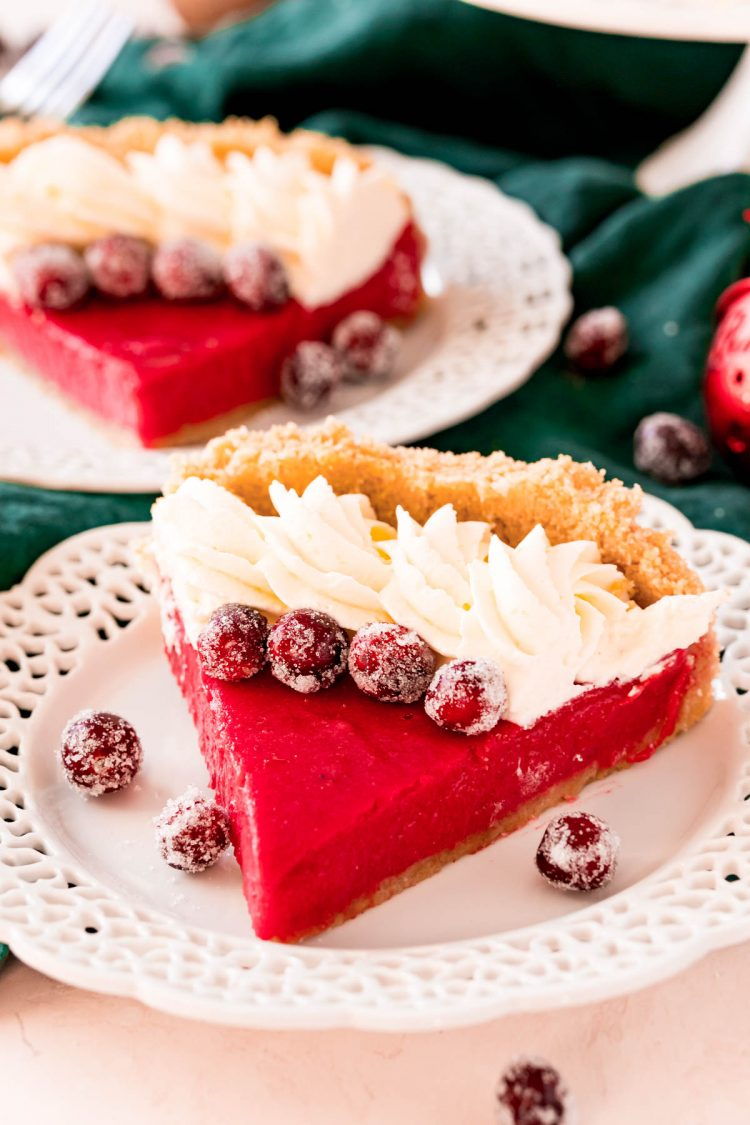 A slice of cranberry pie on a white plate topped with whipped cream and sugared cranberries.