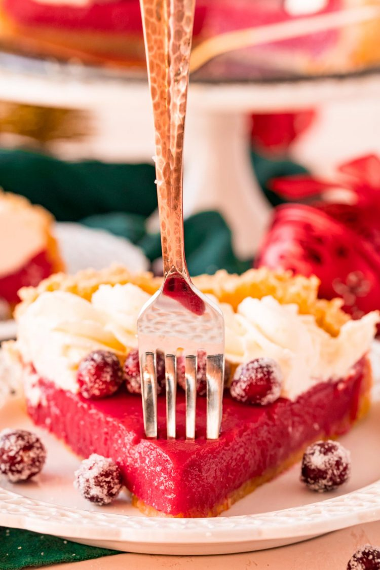 A fork taking a bite out of a cranberry pie.