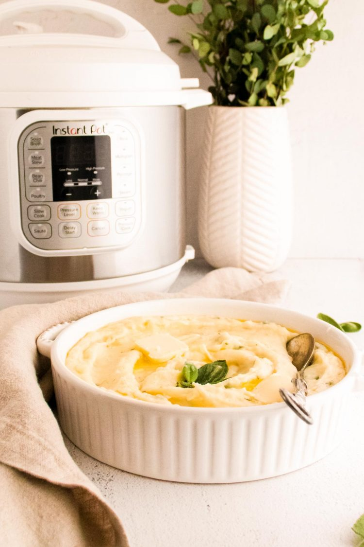 Mashed potatoes in a white serving dish with a white instant-pot and place in the background.