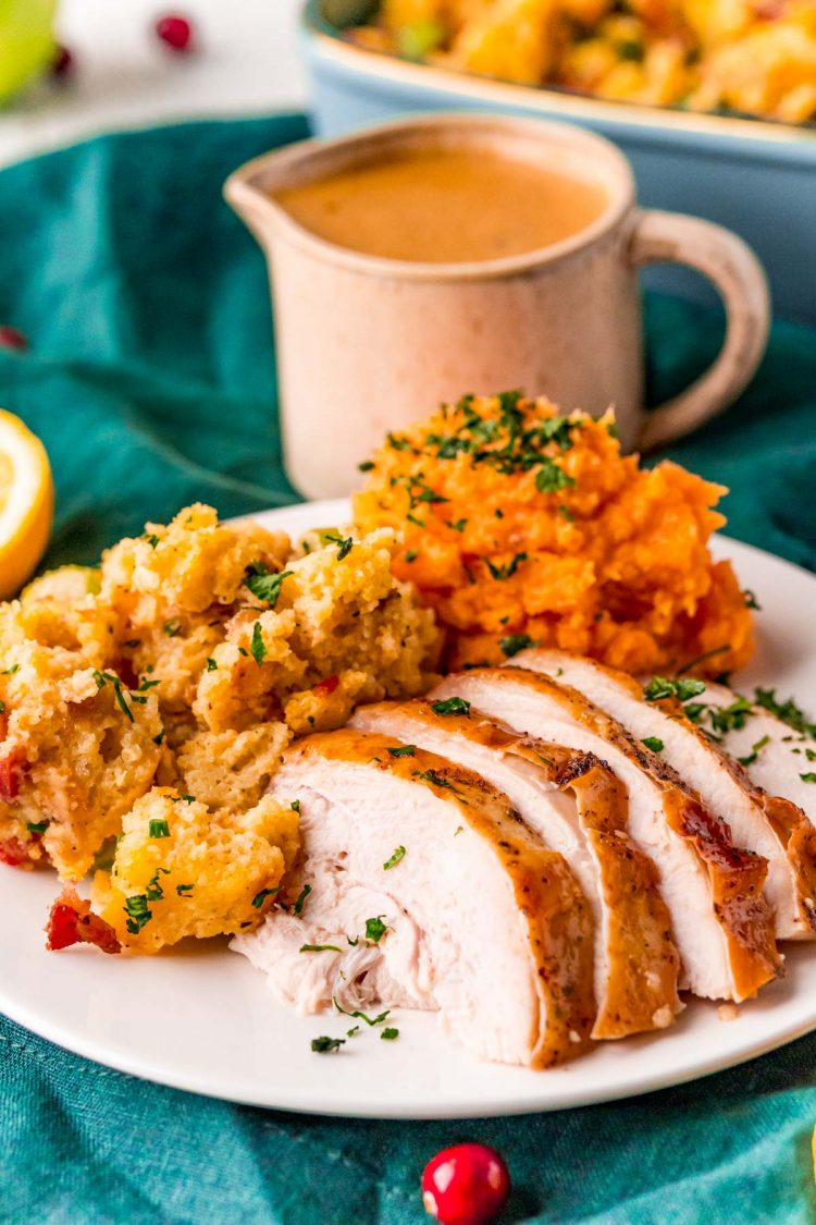 Close up photo of sliced turkey breast on a plate with mashed sweet potatoes and stuffing on the side.