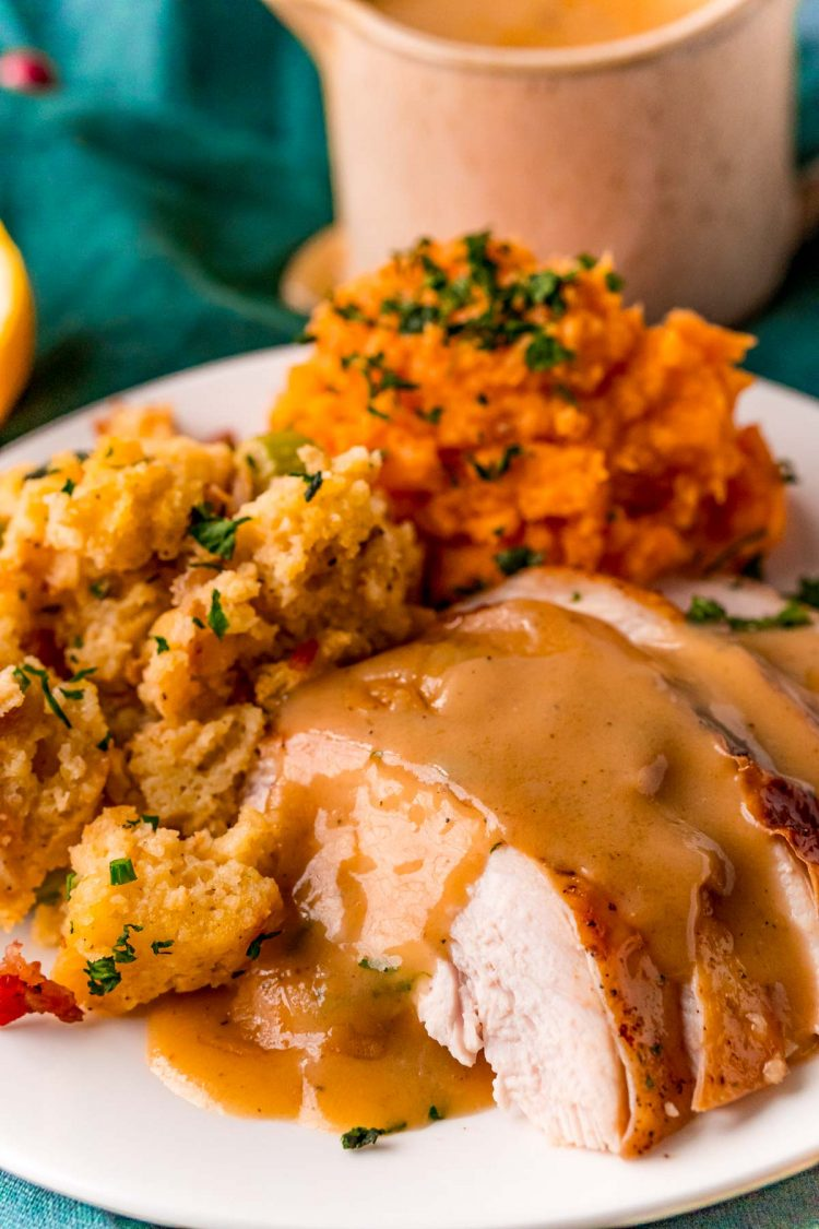 Sliced turkey breast with gravy on top and stuffing and sweet potatoes on the side.