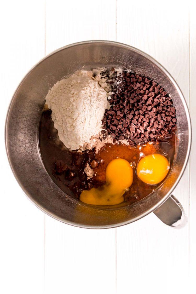 Ingredients to make brownie cookies in a metal mixing bowl.