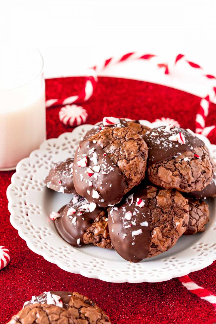 Peppermint chocolate cookies on a white plate with a glass of milk next to it.