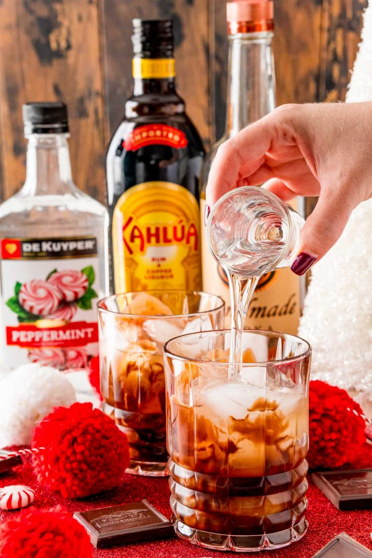 Vodka being poured into a rocks glass with chocolate, ice, and Kahlua.