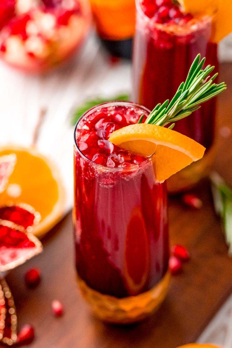 Close up photo of a pomegranate mimosa with orange and rosemary garnish.