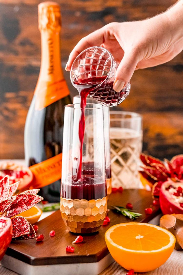 Pomegranate juice being poured into a fluted glass.