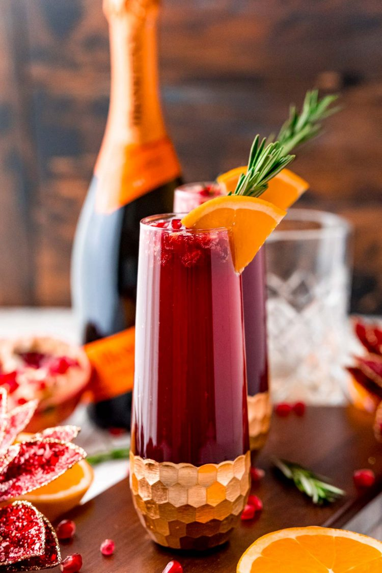 Close up photo of a red mimosa garnished with orange slice and rosemary. Prosecco bottle and pomegranates in the background.