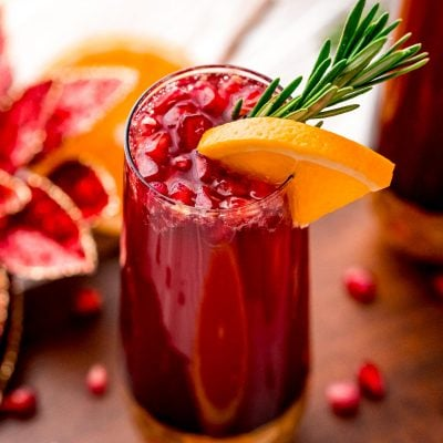 Close up photo of a pomegranate orange mimosa in a gold bottomed champagne glass.