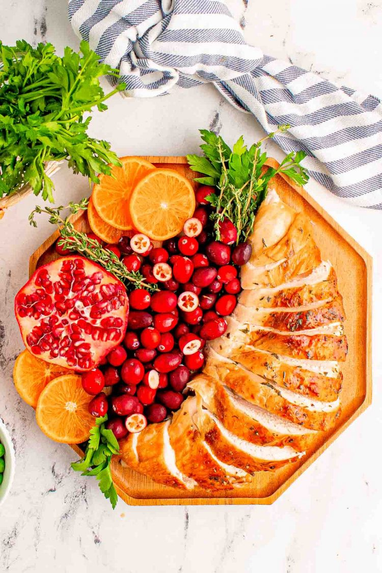 Overhead photo of sliced turkey bread on a wooden plate with cranberries, orange slices, pomegranate, and herbs for garnish.