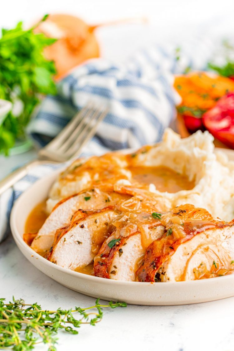 Sliced turkey breast on a white plate with mashed potatoes and gravy.