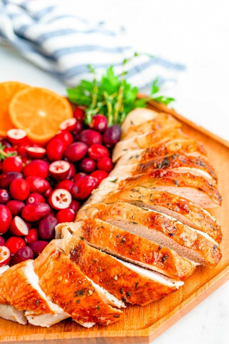 Close up of a sliced turkey breast on a wooden plate with cranberries, orange slices, and herbs for garnish.