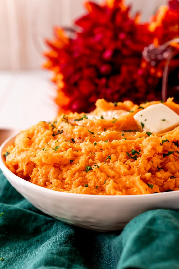 Close up photo of a white bowl filled with sweet potato mash.