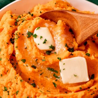 Close up photo of a bowl of mashed sweet potatoes topped with butter with a wooden spoon taking a scoop out of it.