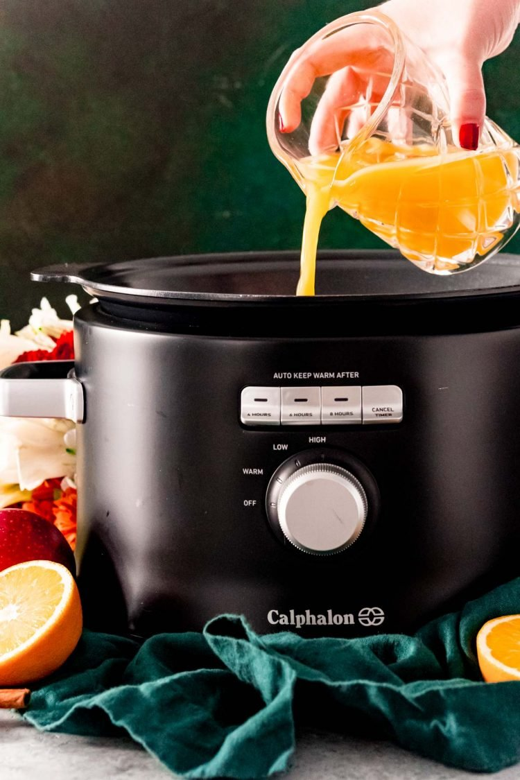 Orange juice being poured into a crock pot to make wassail.
