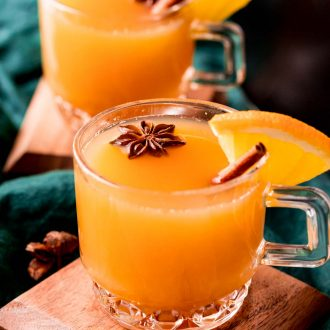 Close up photo of wassail in glass mugs garnished with cinnamon sticks and star anise.