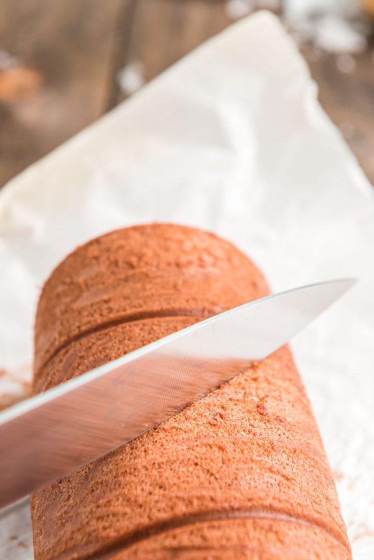 A knife cutting a diagonal slice in a chocolate cake roll for a buche de noel.