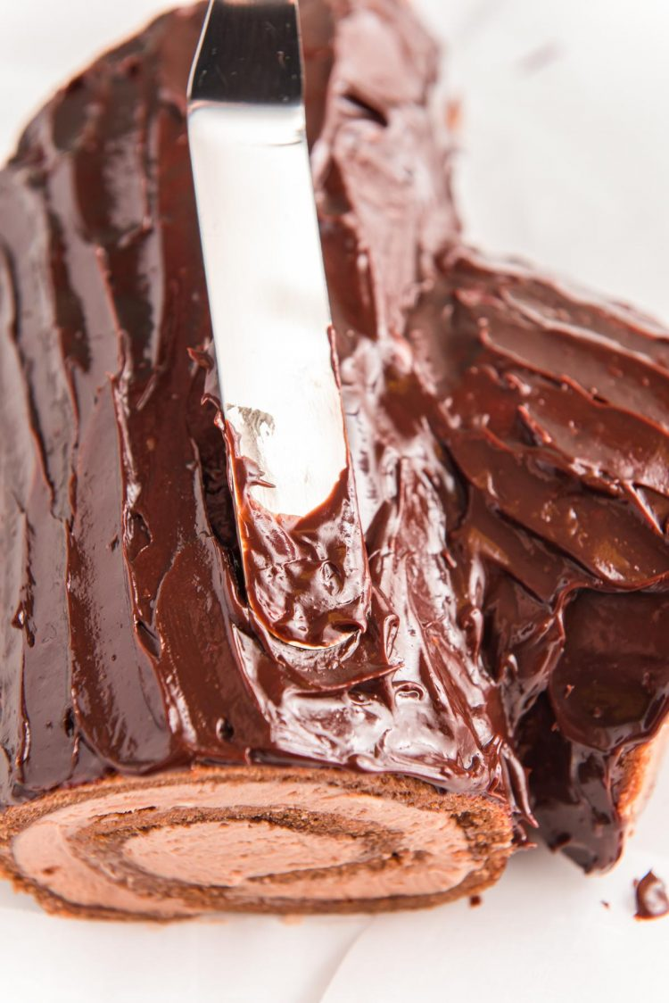 Chocolate ganache being spread over the top of a cake roll to make a buche de noel yule log cake.