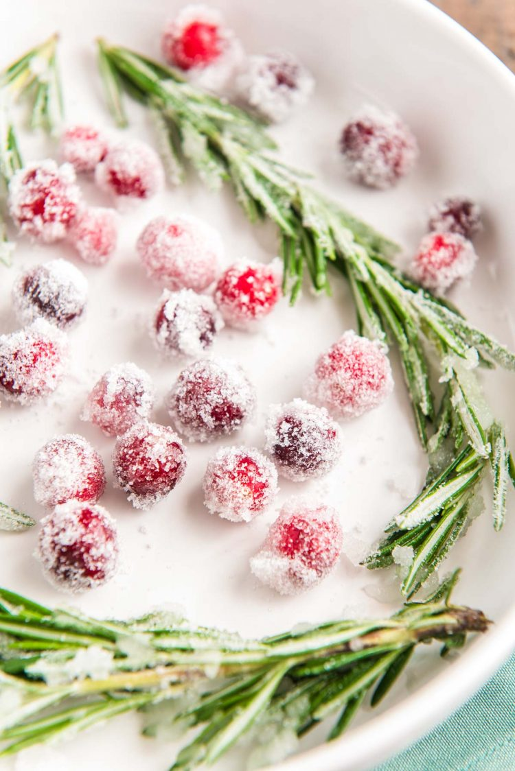 Cranberries and rosemary dipping in simple syrup and sugar.