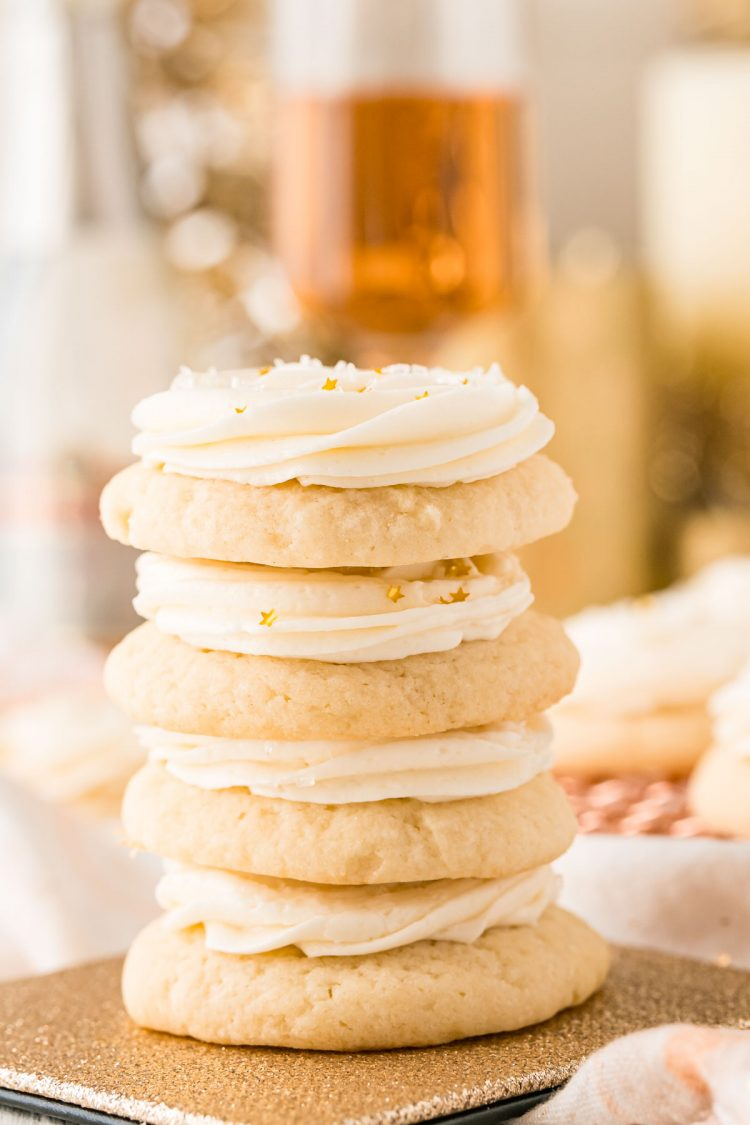 Close up photo of 4 sugar cookies stacked on top of each other with a glass of champagne in the background.
