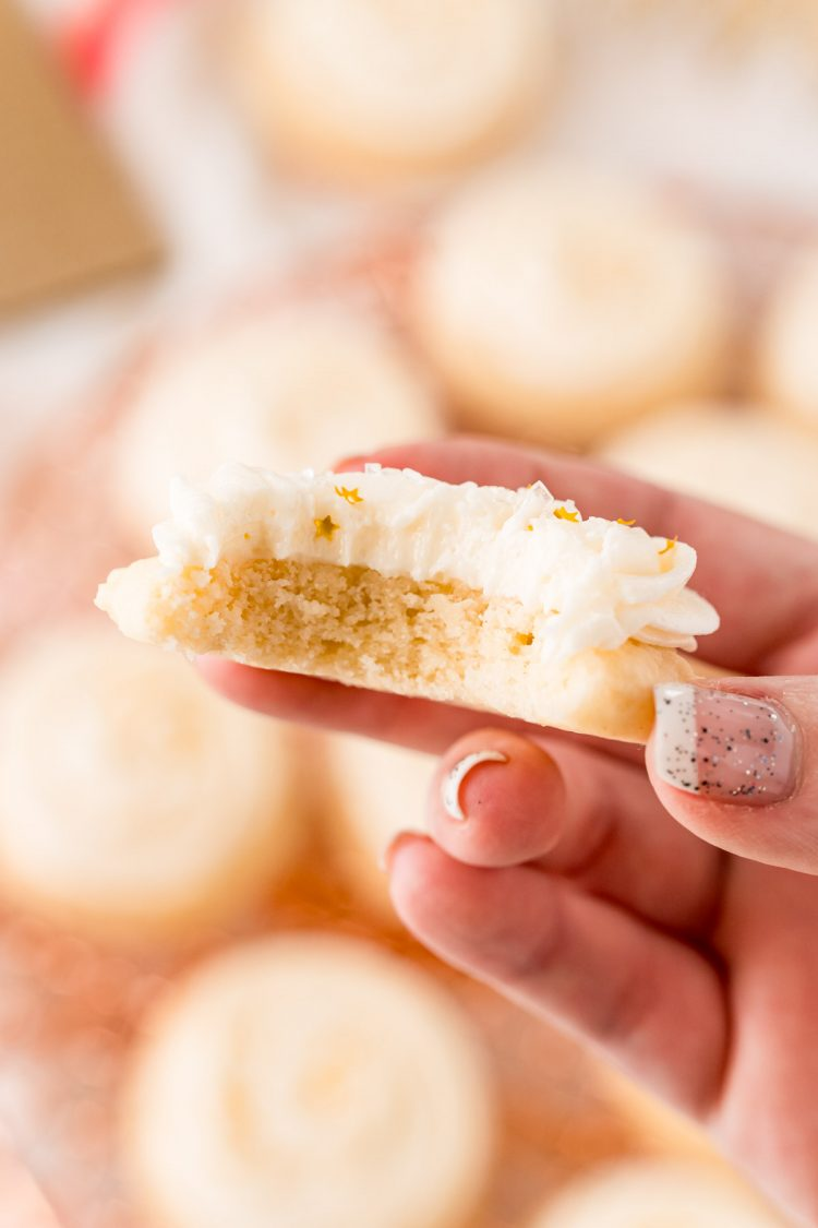 A woman's hand holding a sugar cookie with a bite taken out of it.