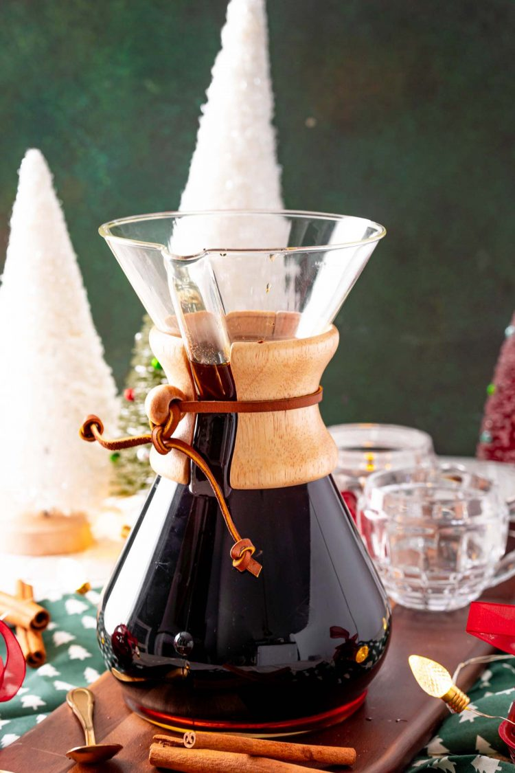 A carafe of coffee with Christmas decorations on the table.