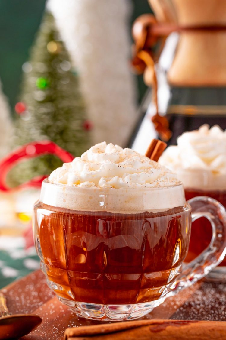 Close up photo of a mug of hot coffee topped with whipped cream at christmastime.