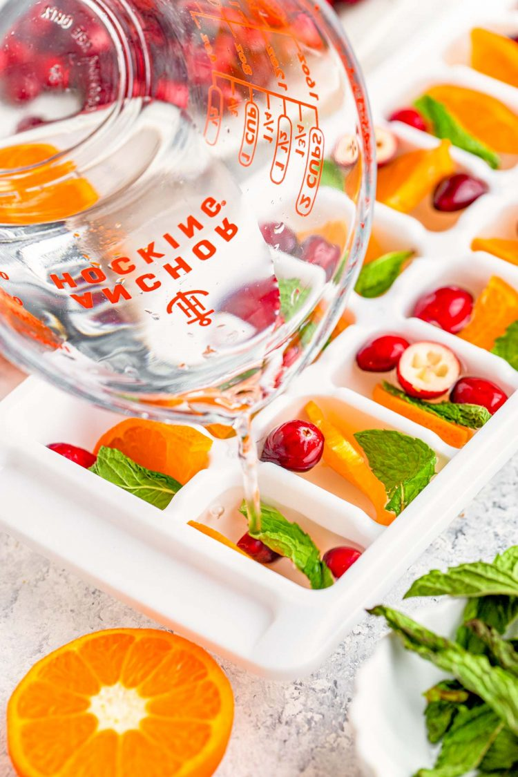 Water being poured into ice cube trays with cranberries, mint, and orange.