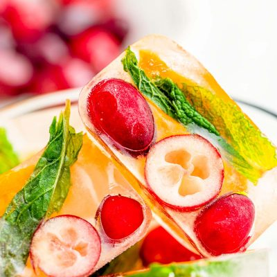 Close up photo of ice cubes with cranberries, orange, and mint in them