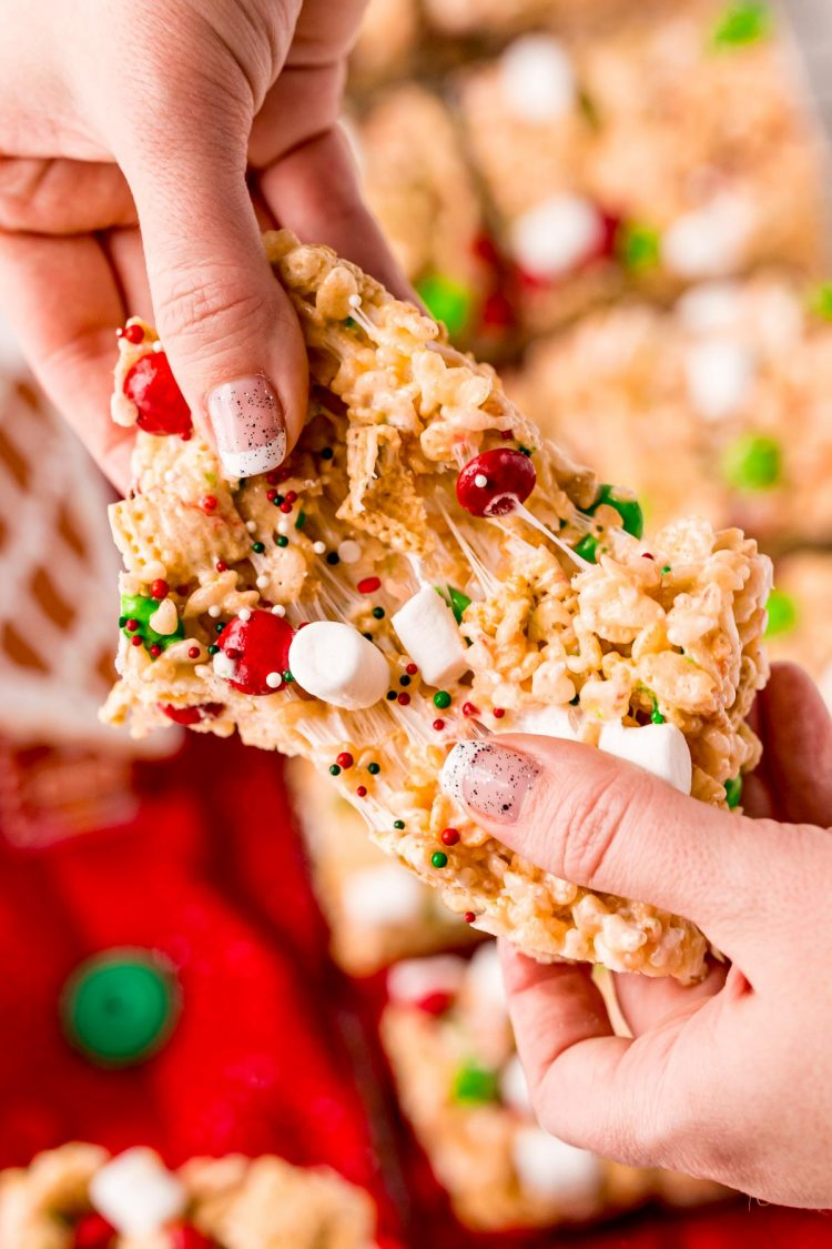 A woman's hand pulling apart a Christmas rice krispie treat.