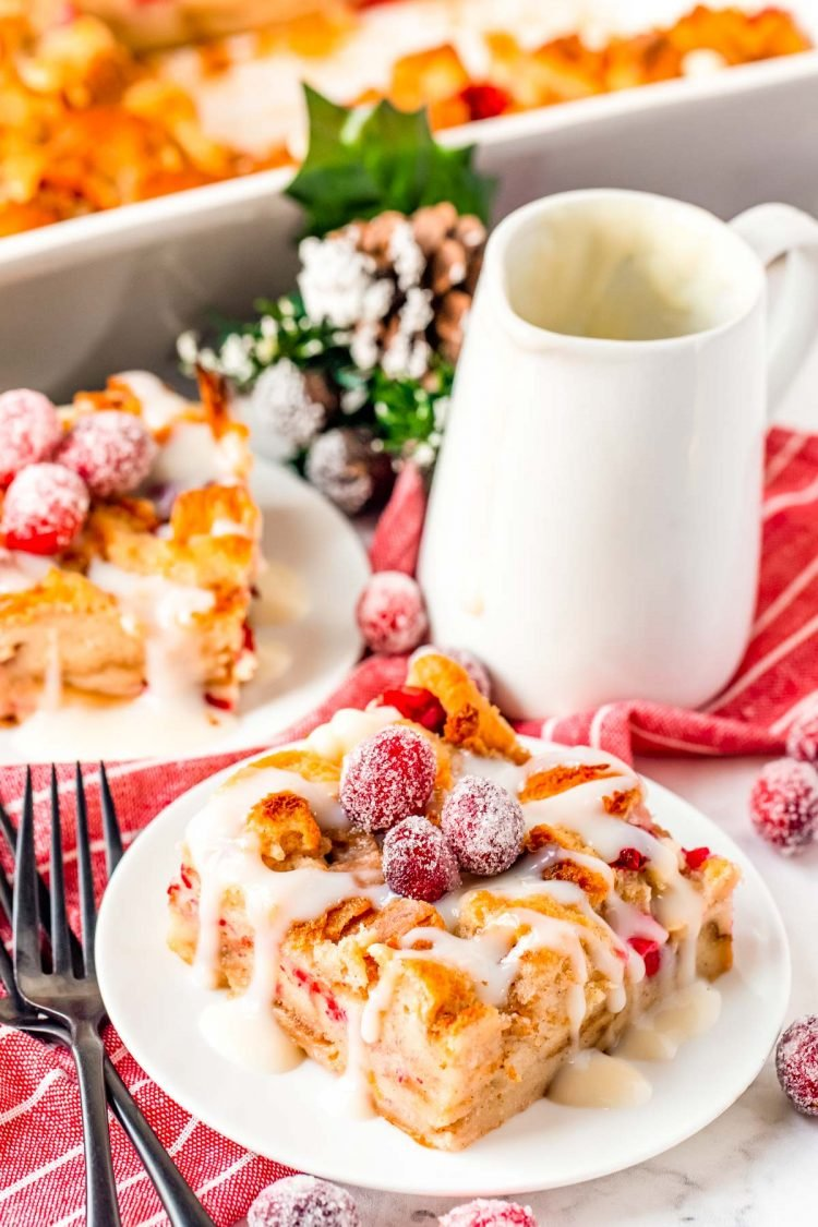 Close up photo of cranberry white chocolate bread pudding on a white plate.